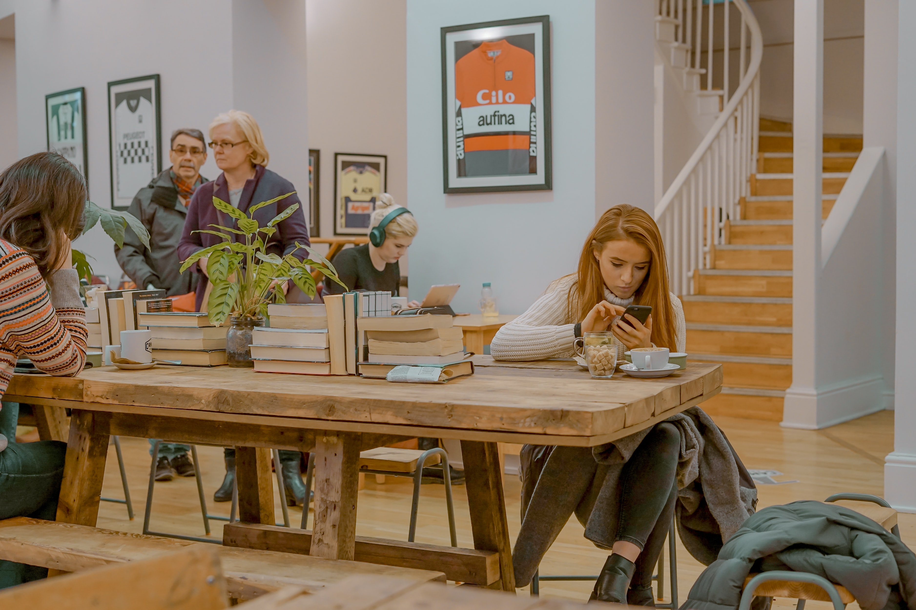 woman sitting on chair near table holding smartphone surrounded with people inside house