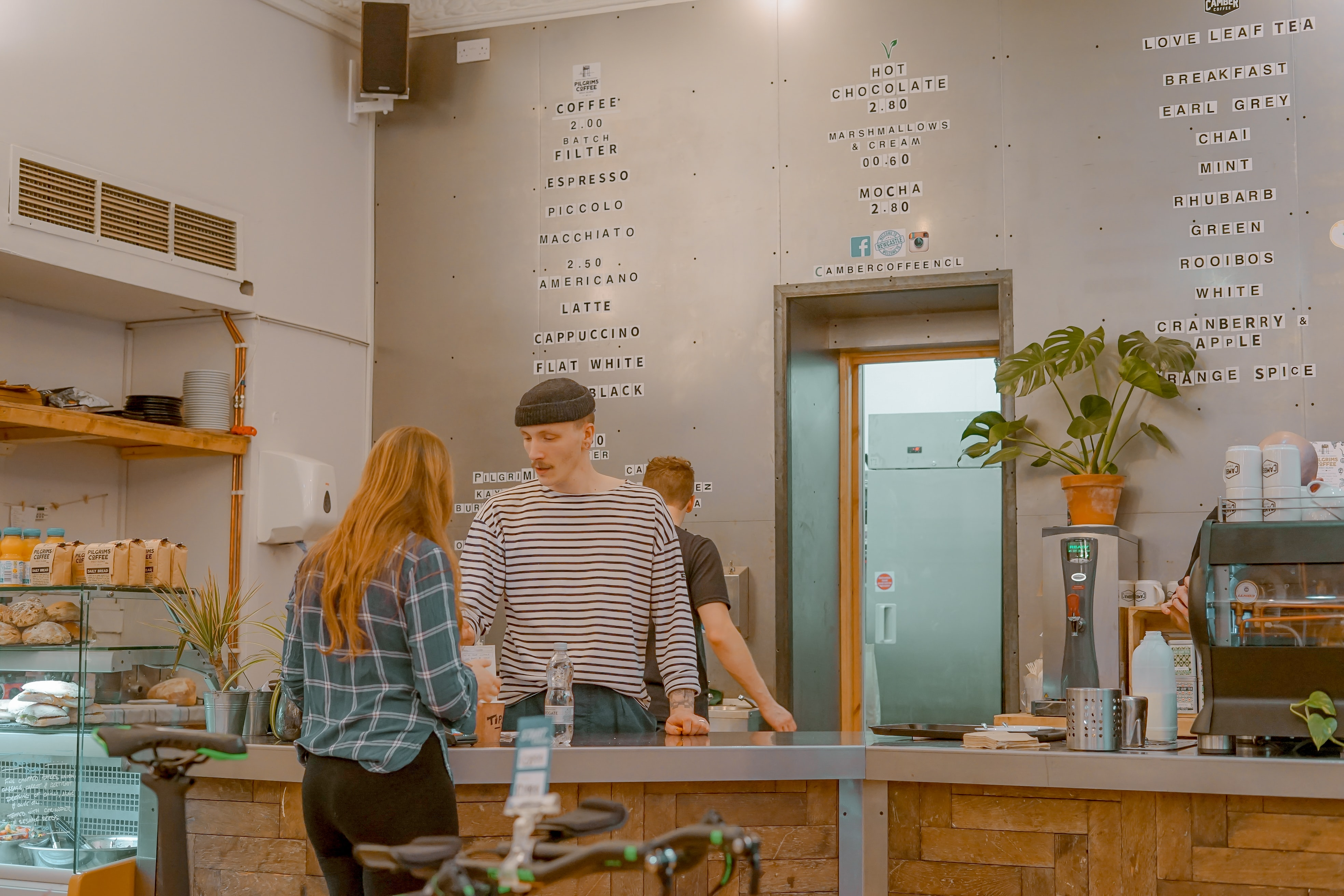 man and woman talking in front of gray tabletop inside shop