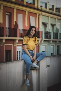 woman in yellow shirt sitting on terrace rail during daytime
