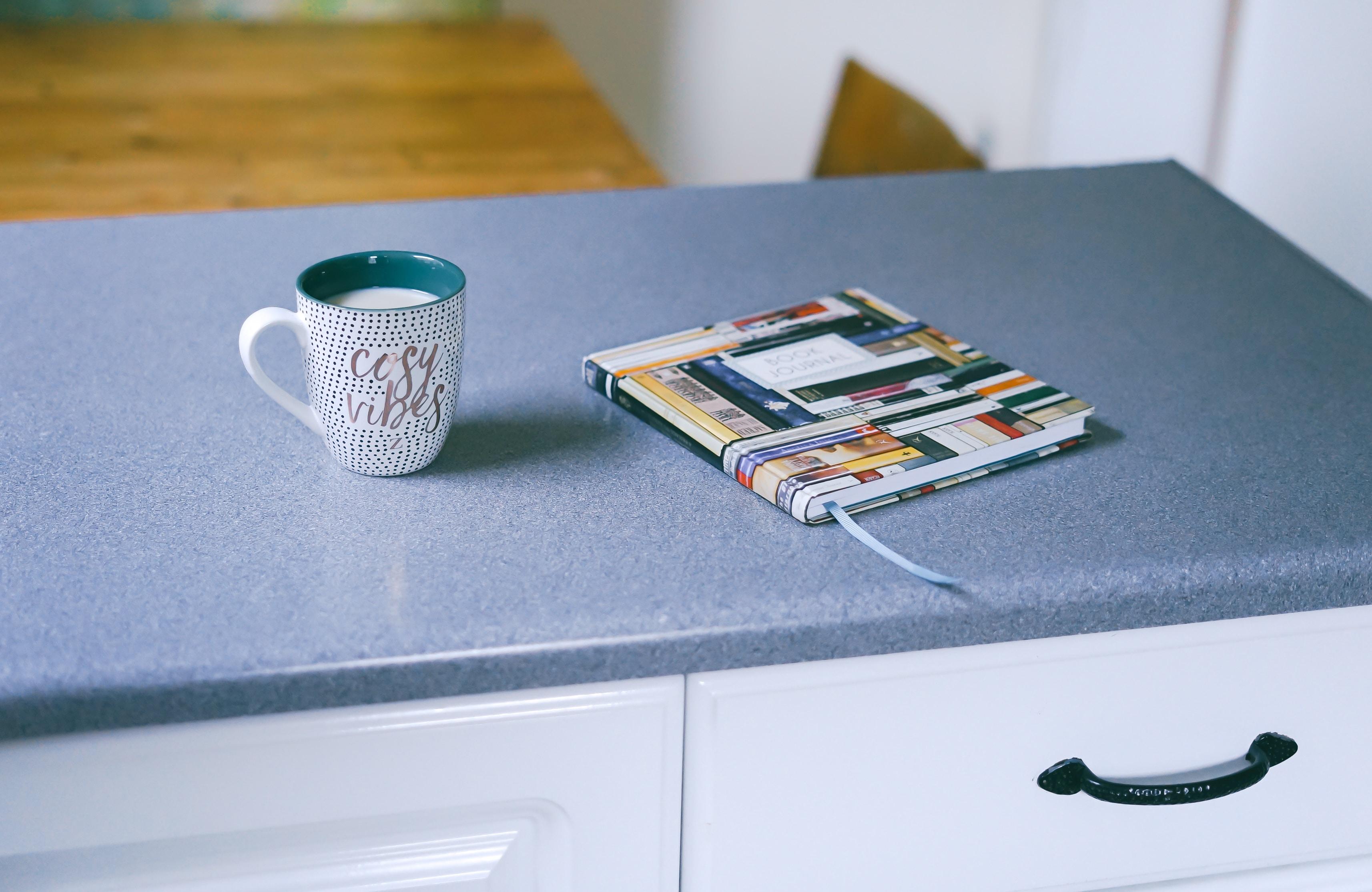 gray and white ceramic mug beside multicolored covered book