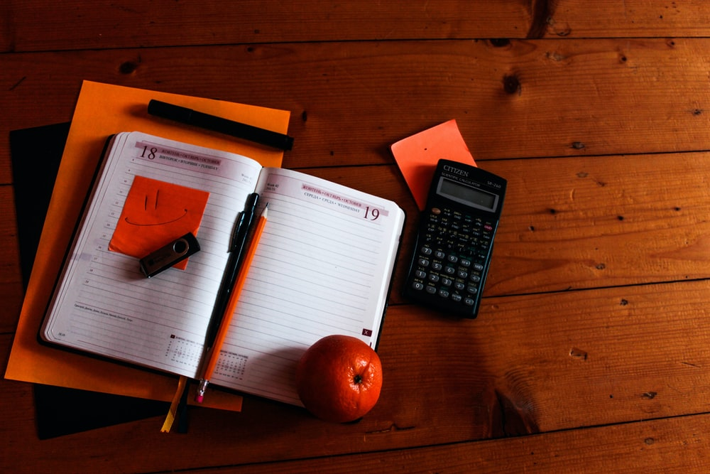 black scientific calculator, orange, and notebook on table