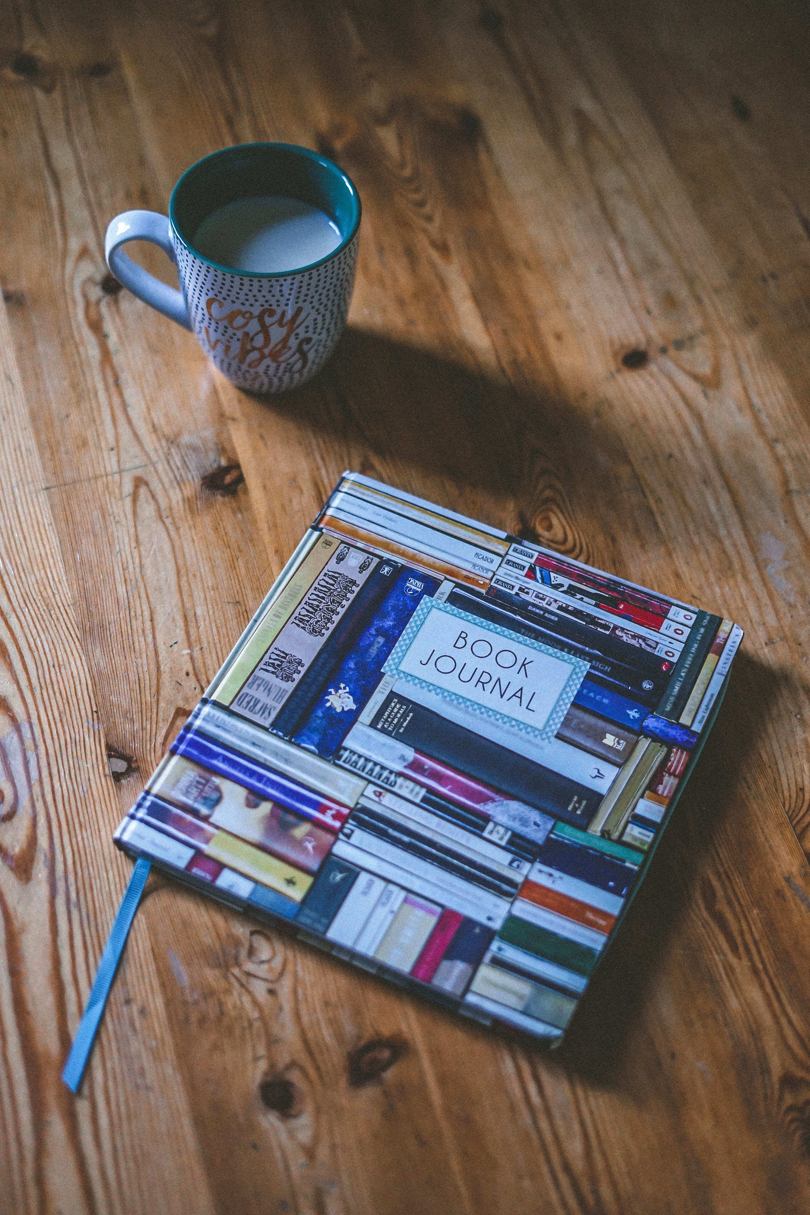 Book Journal near white and multicolored ceramic mug on wooden surface
