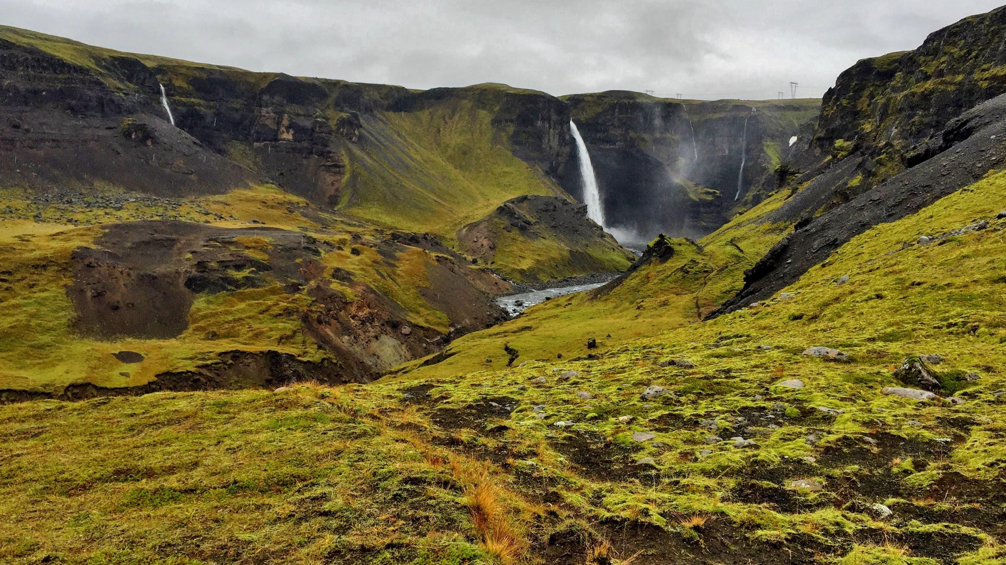 waterfalls near grass field during daytime