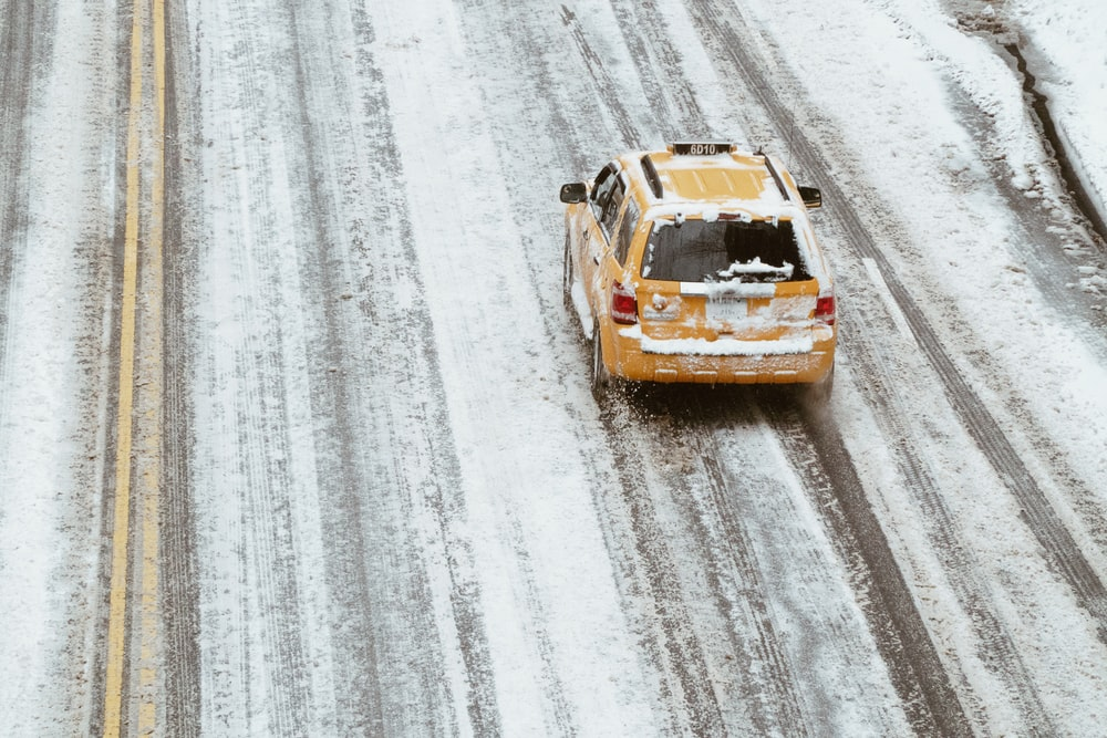 aerial shot of yellow car on the road