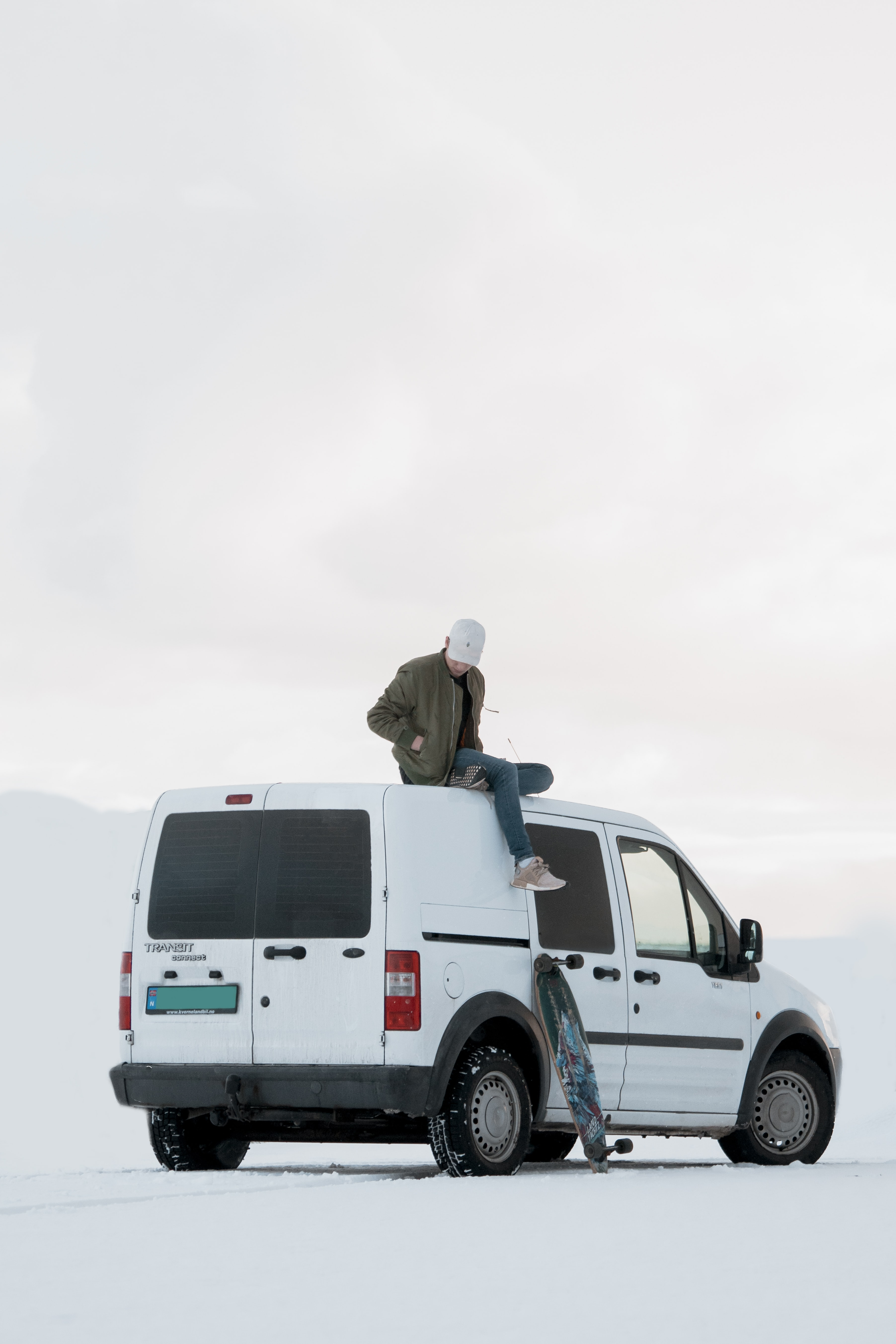 man sitting on top of white minivan during daytime