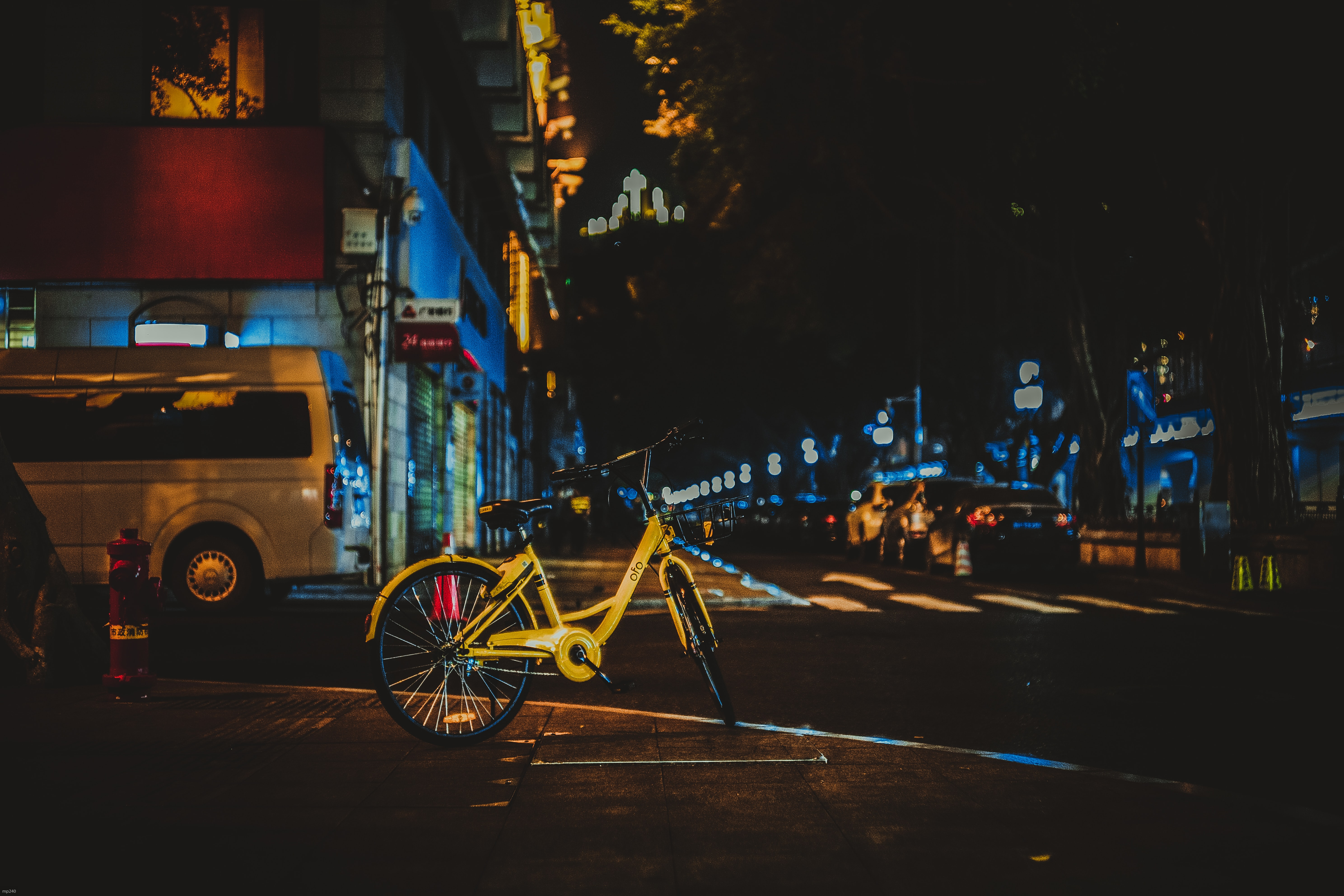 yellow bicycle park beside road during nighttime