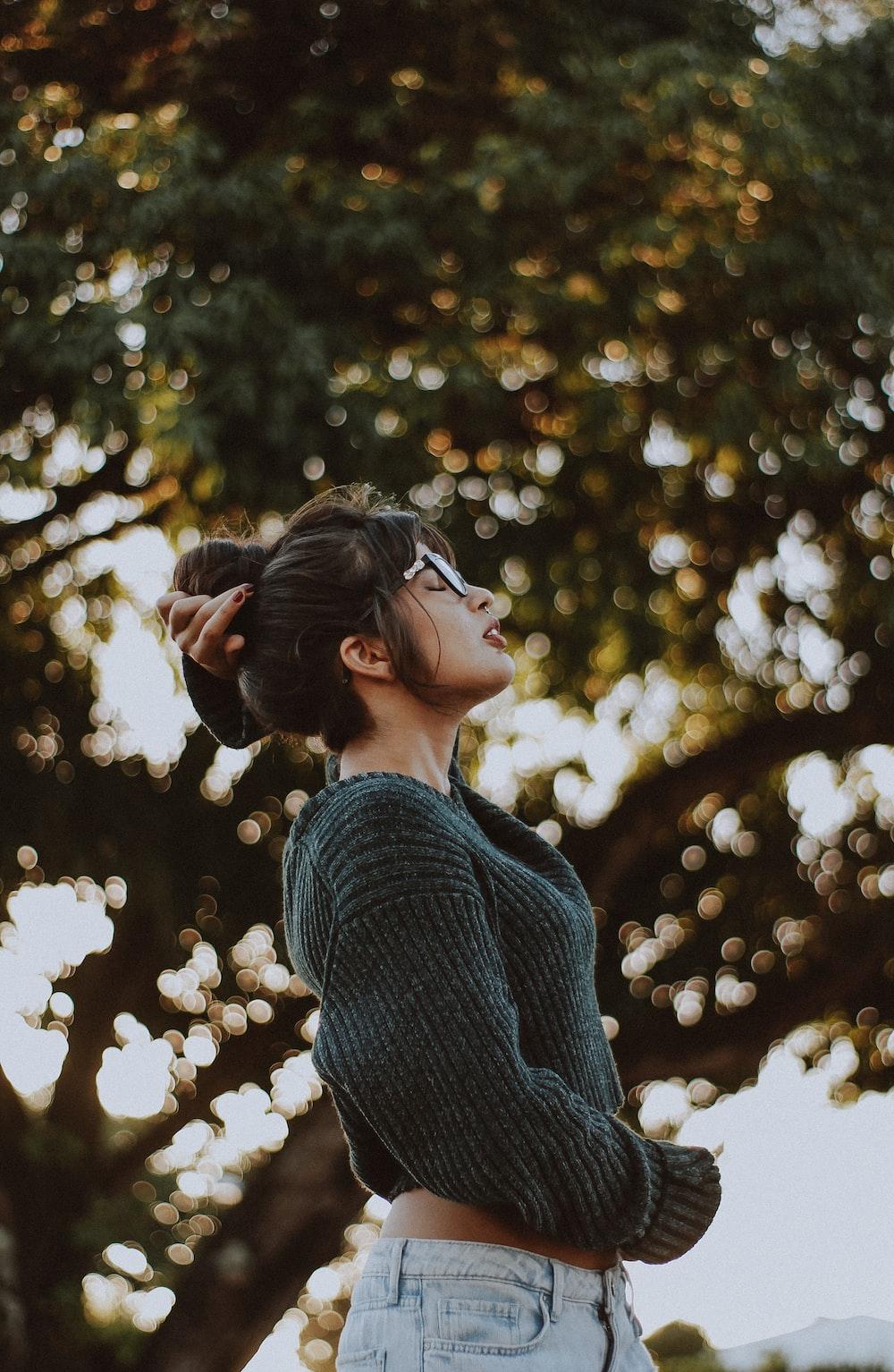 mujer vestida con suéter gris cerca de árbol