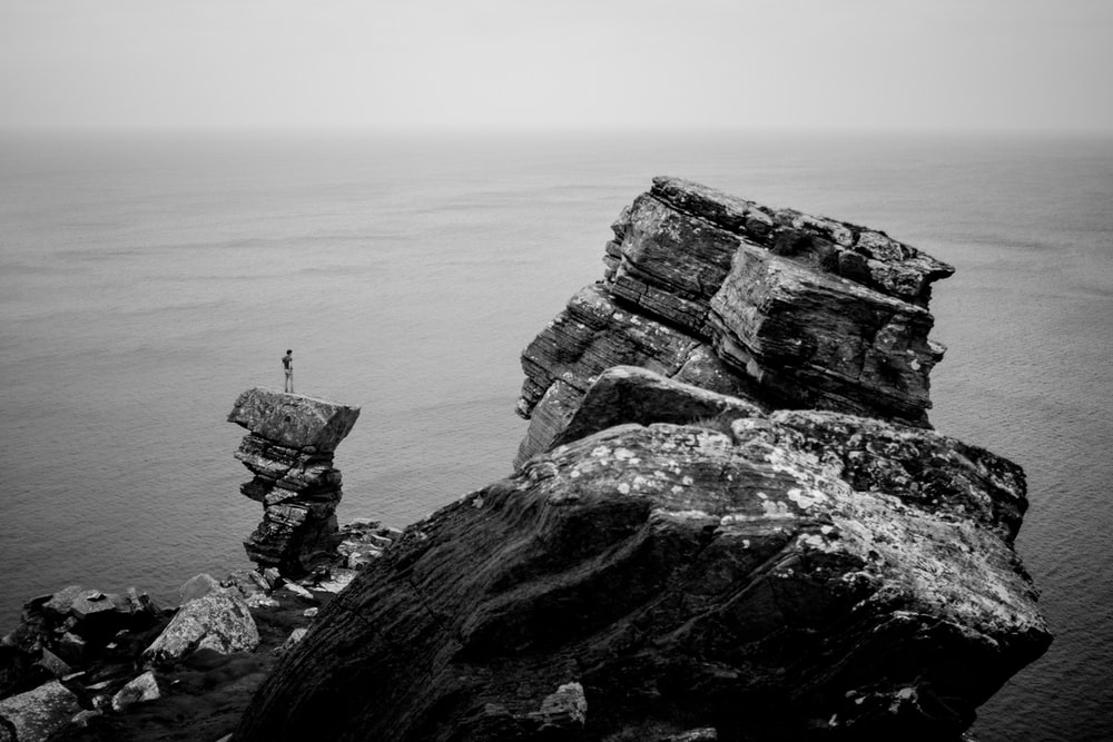 grayscale photography of a person standing on cliff near the ocean