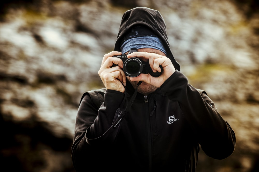 man wearing hoodie taking pictures selective focus photography