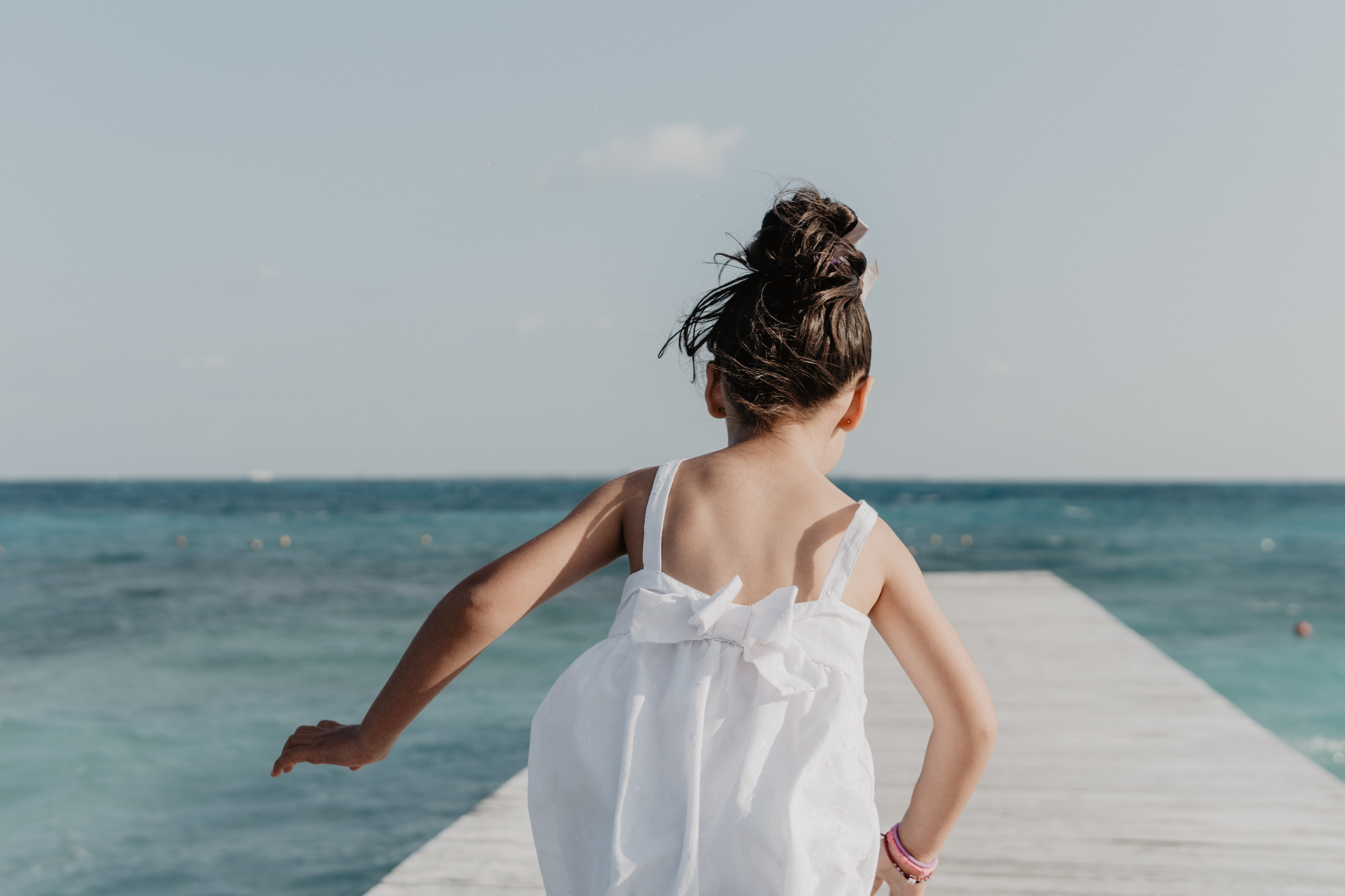 girl running on dock under white sky