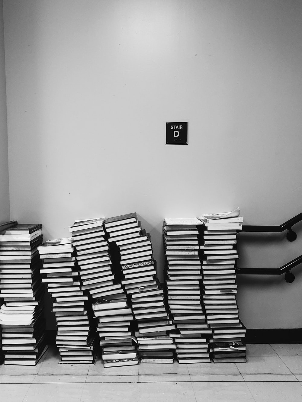 grayscale photography of pile of books
