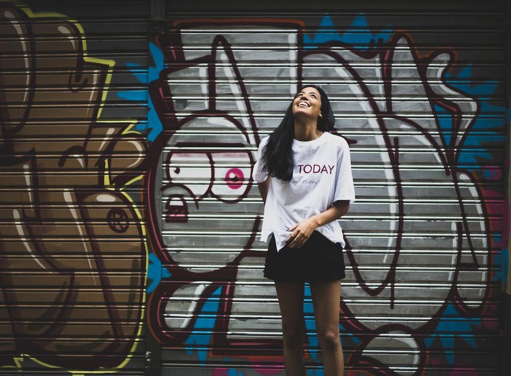 woman standing beside graffiti wall taken at daytime