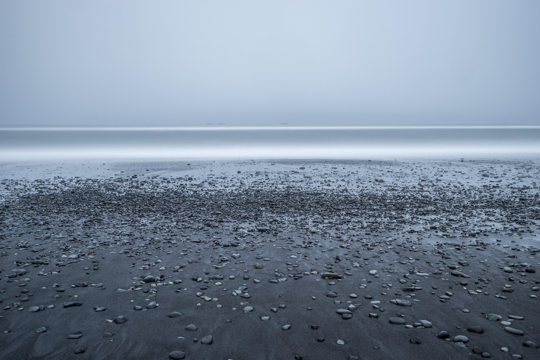 rocky beach with grey skies above sea