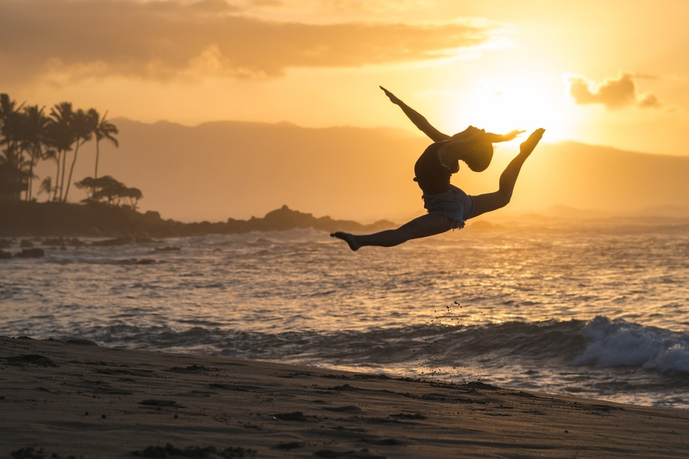 silhouette of woman jumping on sea shore