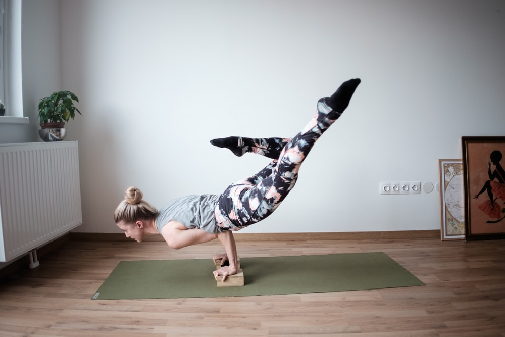 woman balancing her body on olive-green mat