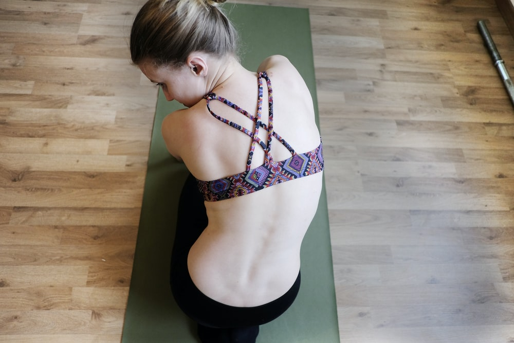 woman in purple sports bra doing yoga