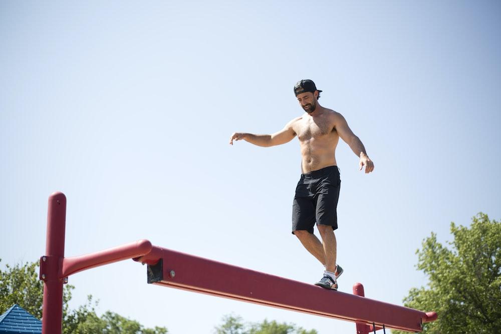man wearing black shorts walking on red metal beam