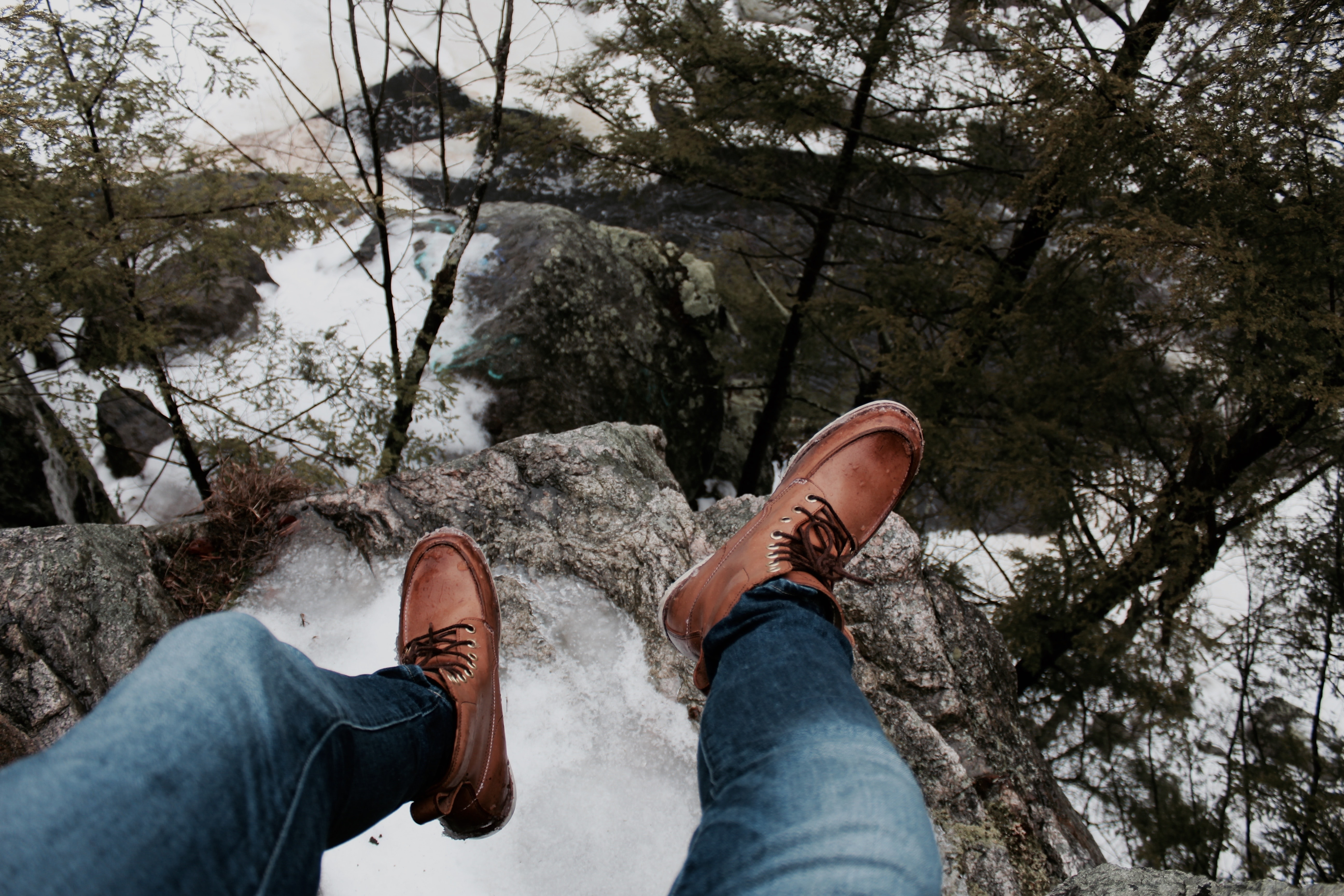 person sitting on the edge of the cliff