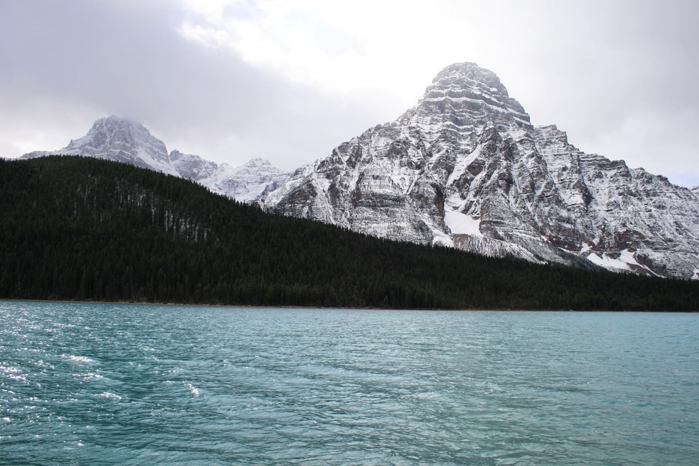snow covered mountains near body of water