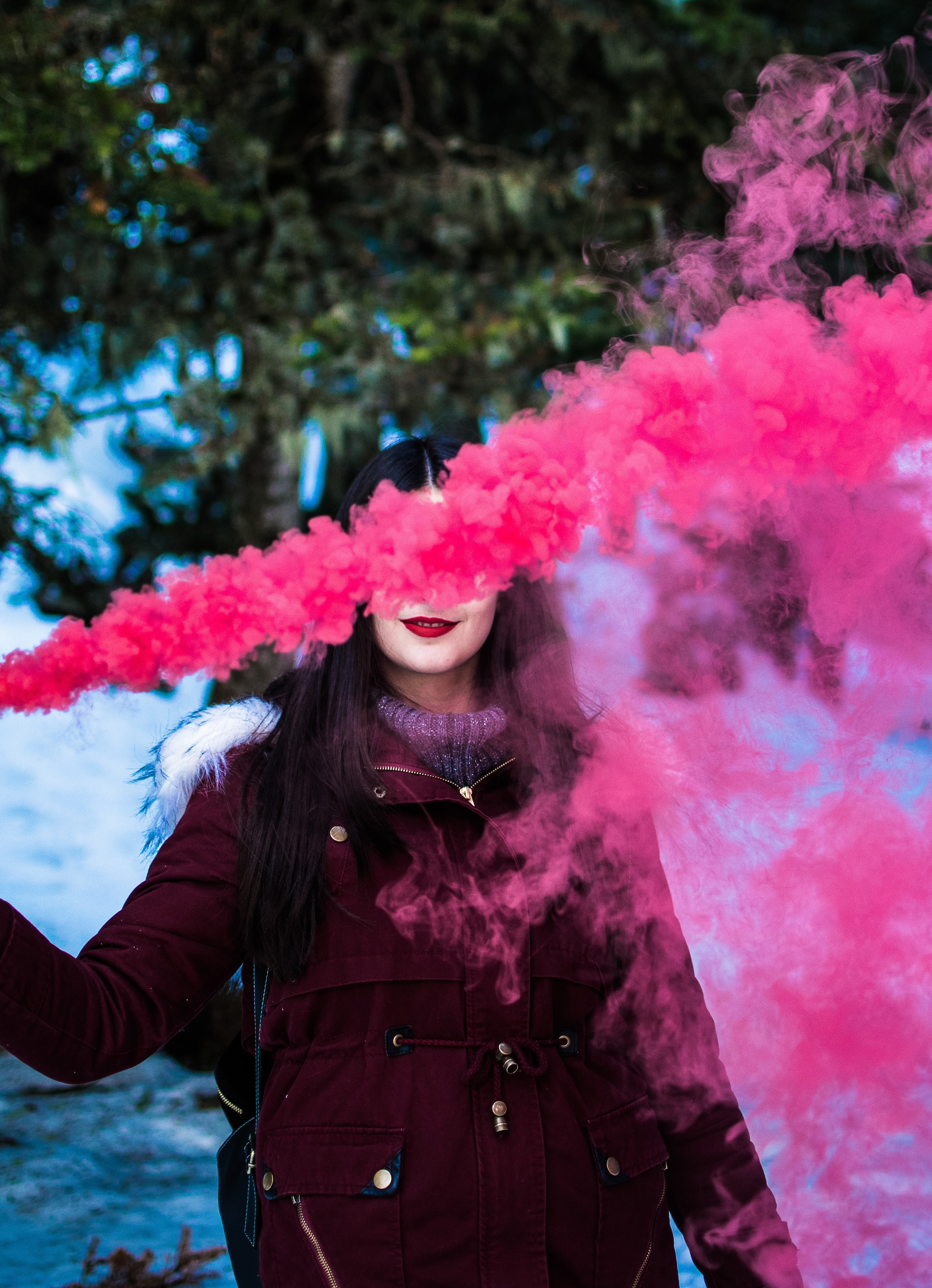 woman in red parka using smoke screen