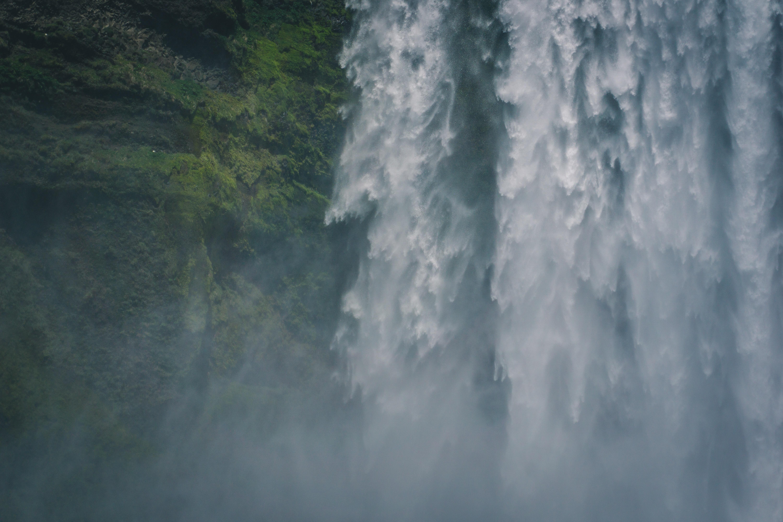 waterfalls near green trees at daytime