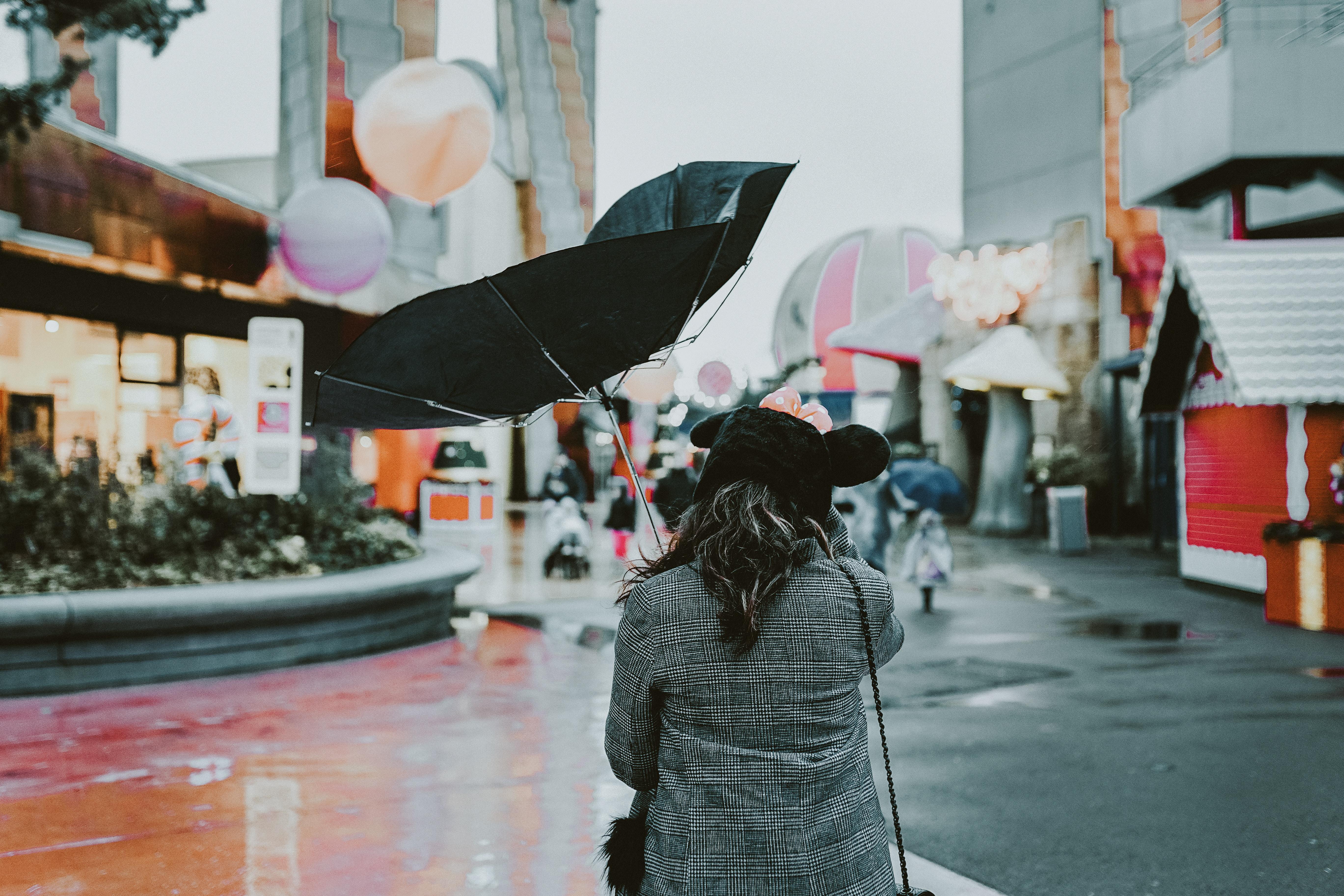 person holding black umbrella during daytime