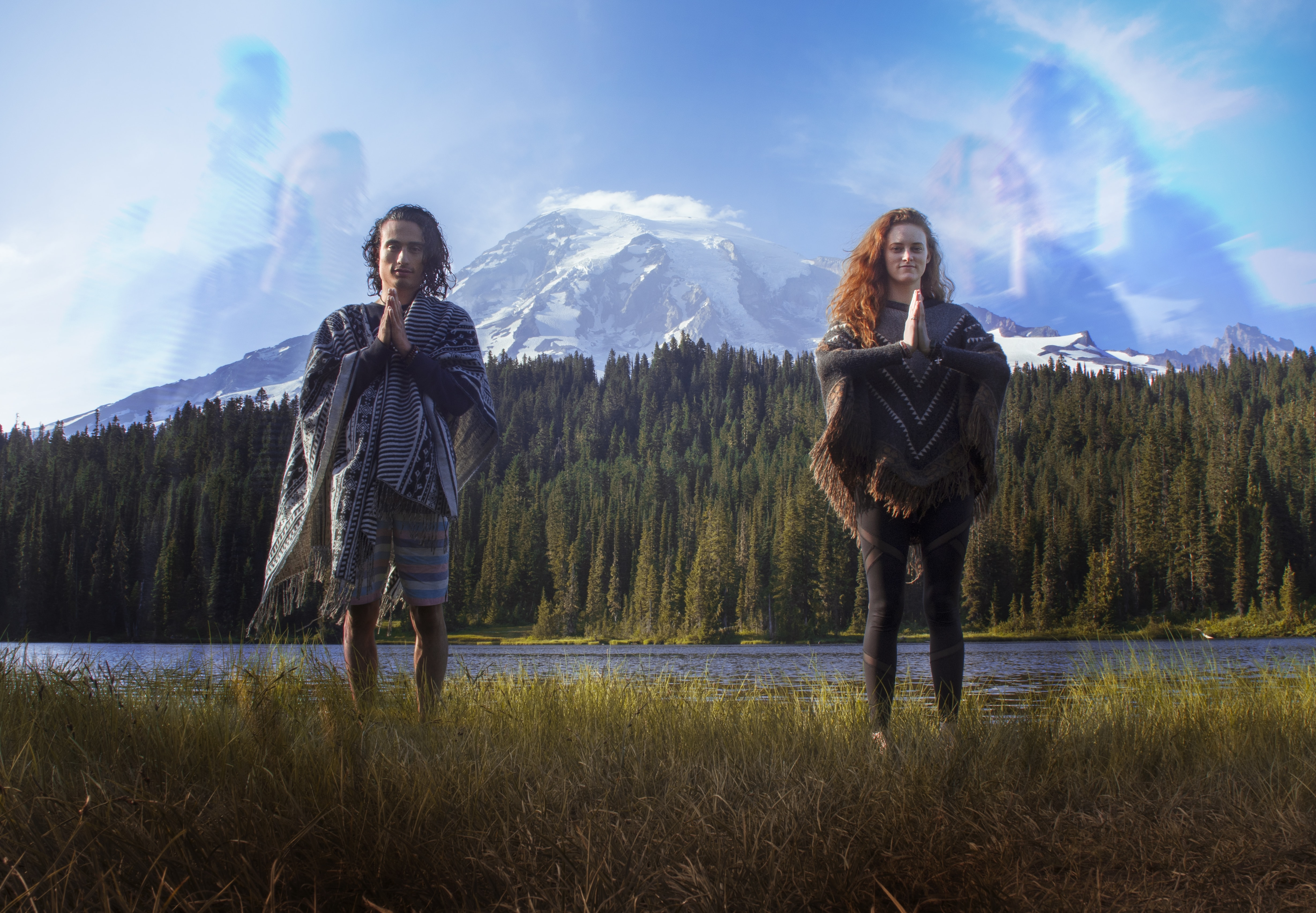man and woman standing on green grass with snow-capped mountain at distance