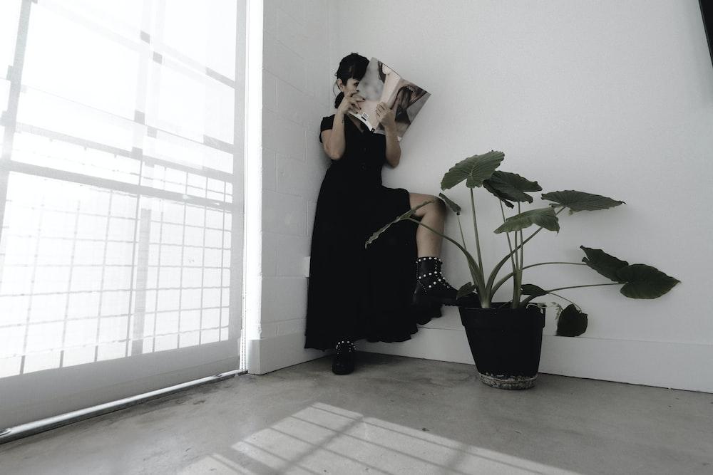woman in black dress reading book
