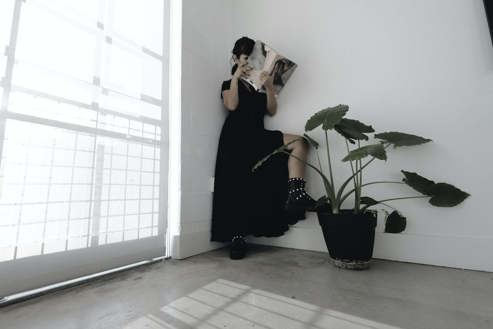 woman in black dress reading book