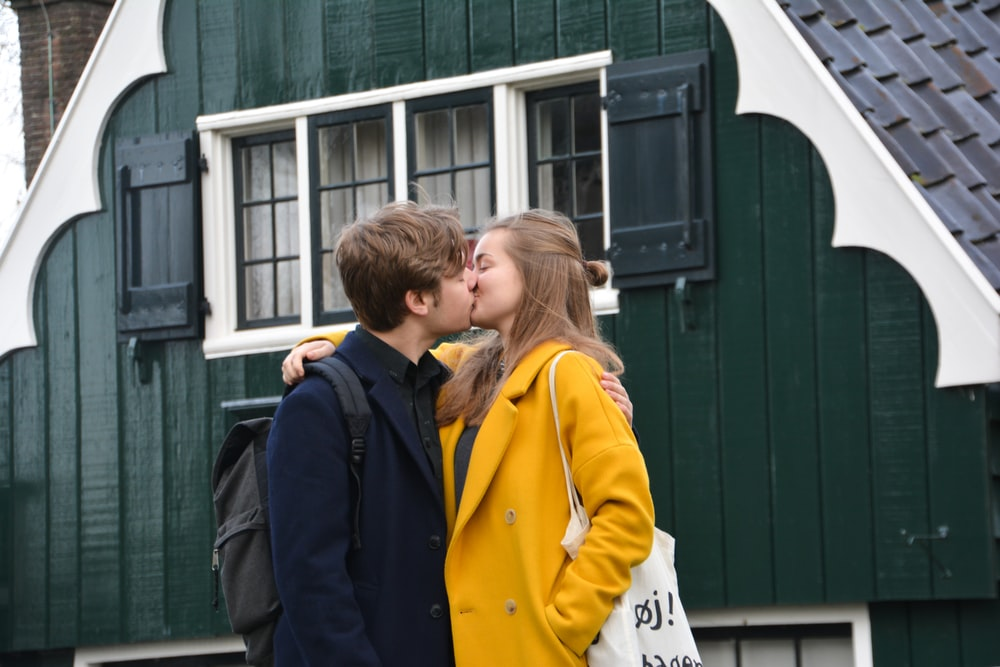 man and woman kissing each other in front of green house during daytime