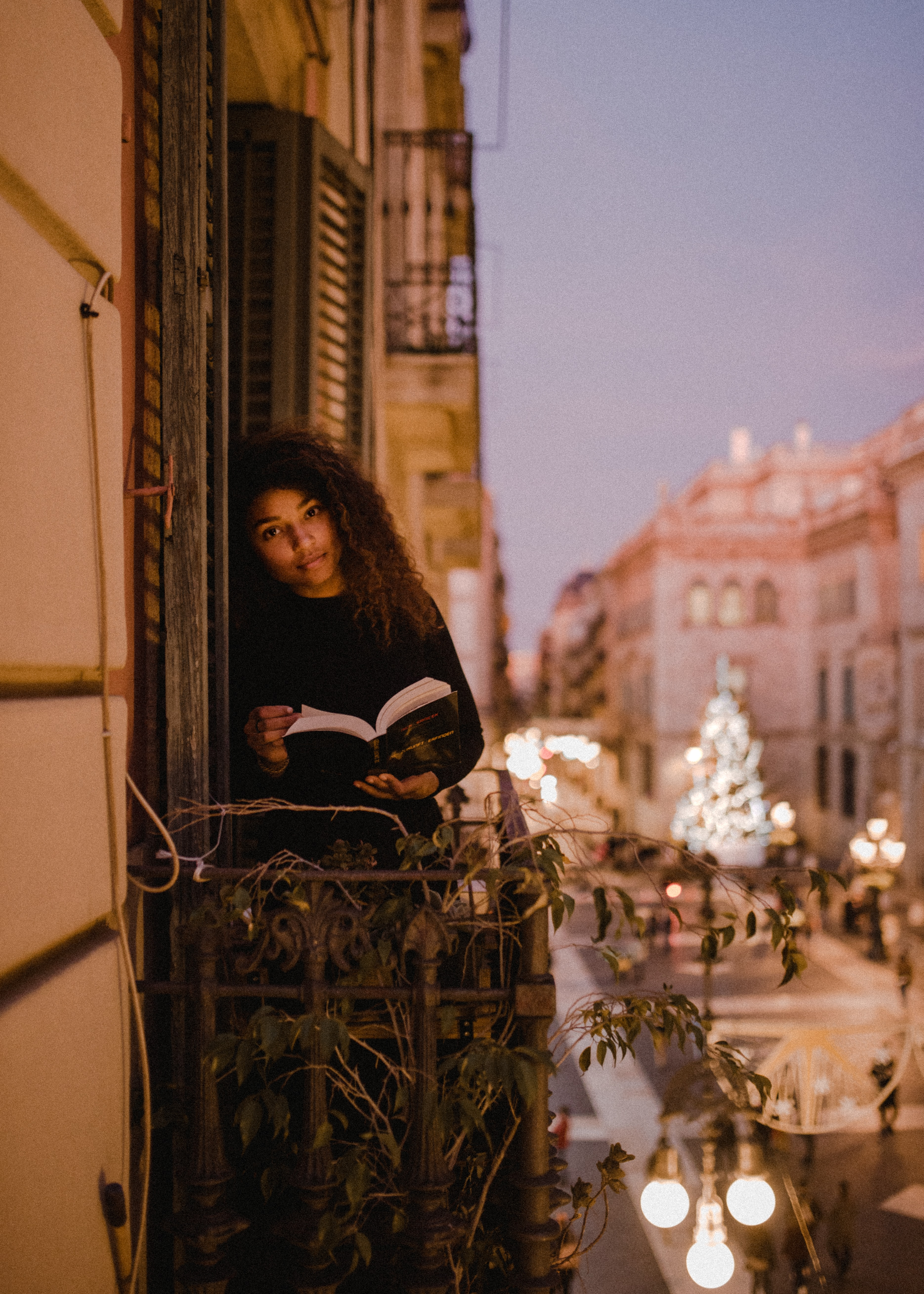 woman holding book standing on terrace during daytime