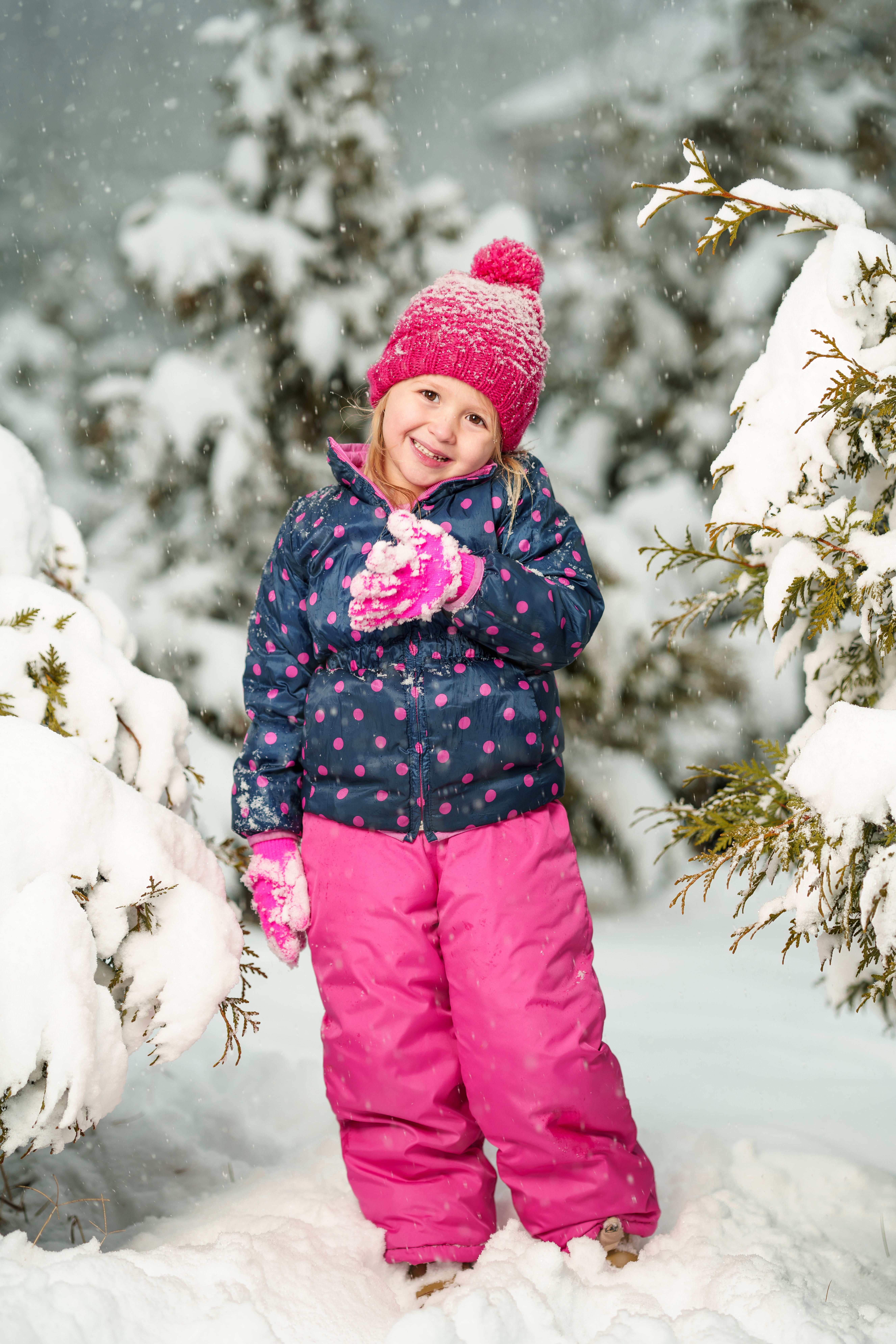 girl standing on white snow while smiling near trees covered with snow