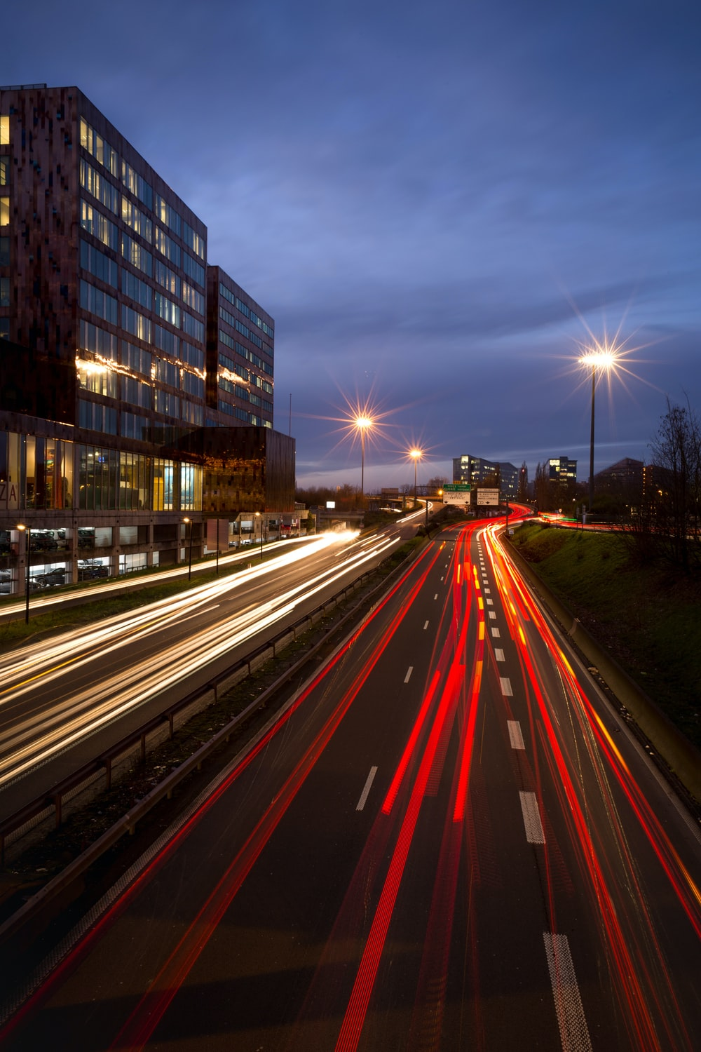 time lapse photography of road beside high-rise building