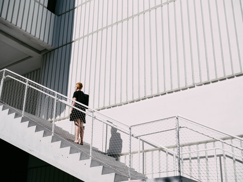 woman standing on stairway during daytime