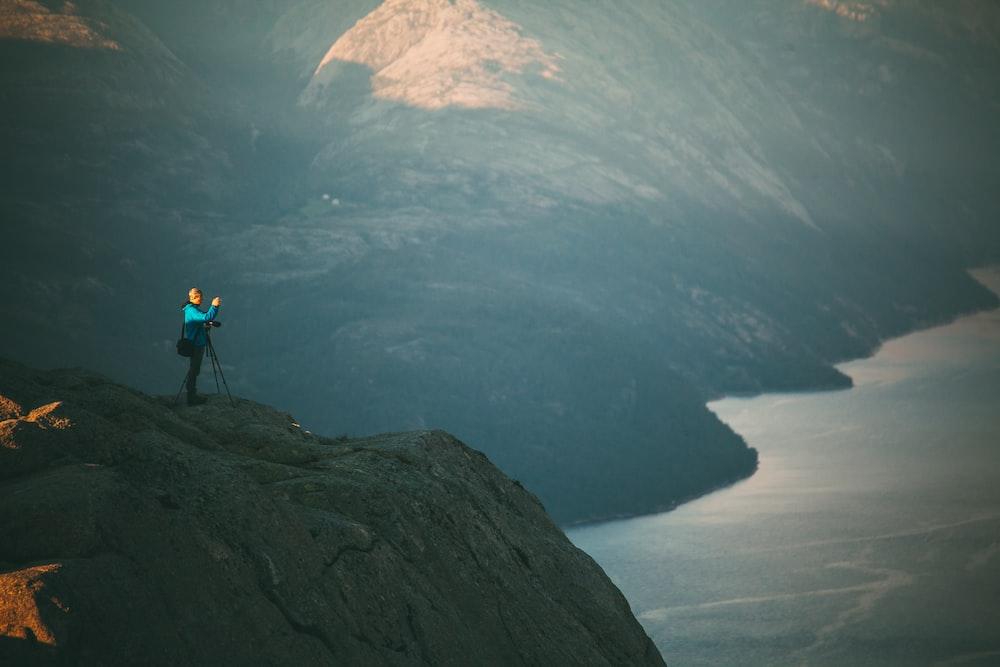 man standing on hill near lake