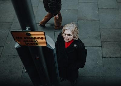 woman beside post near street