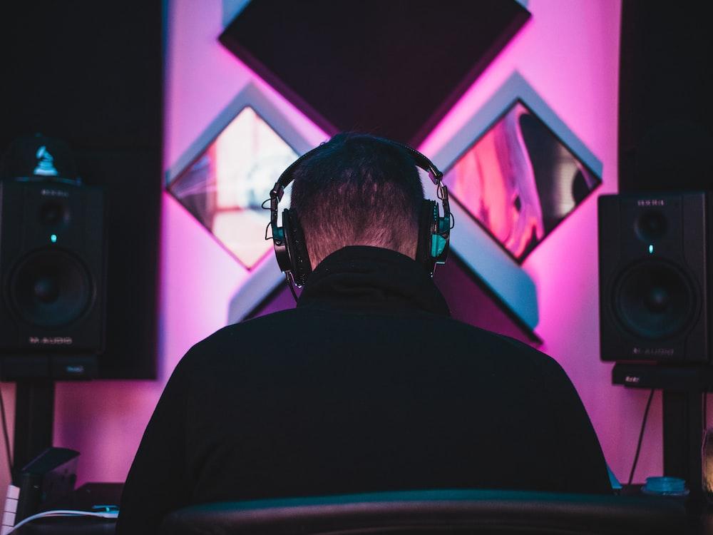 man wearing black headphones near two PA speakers