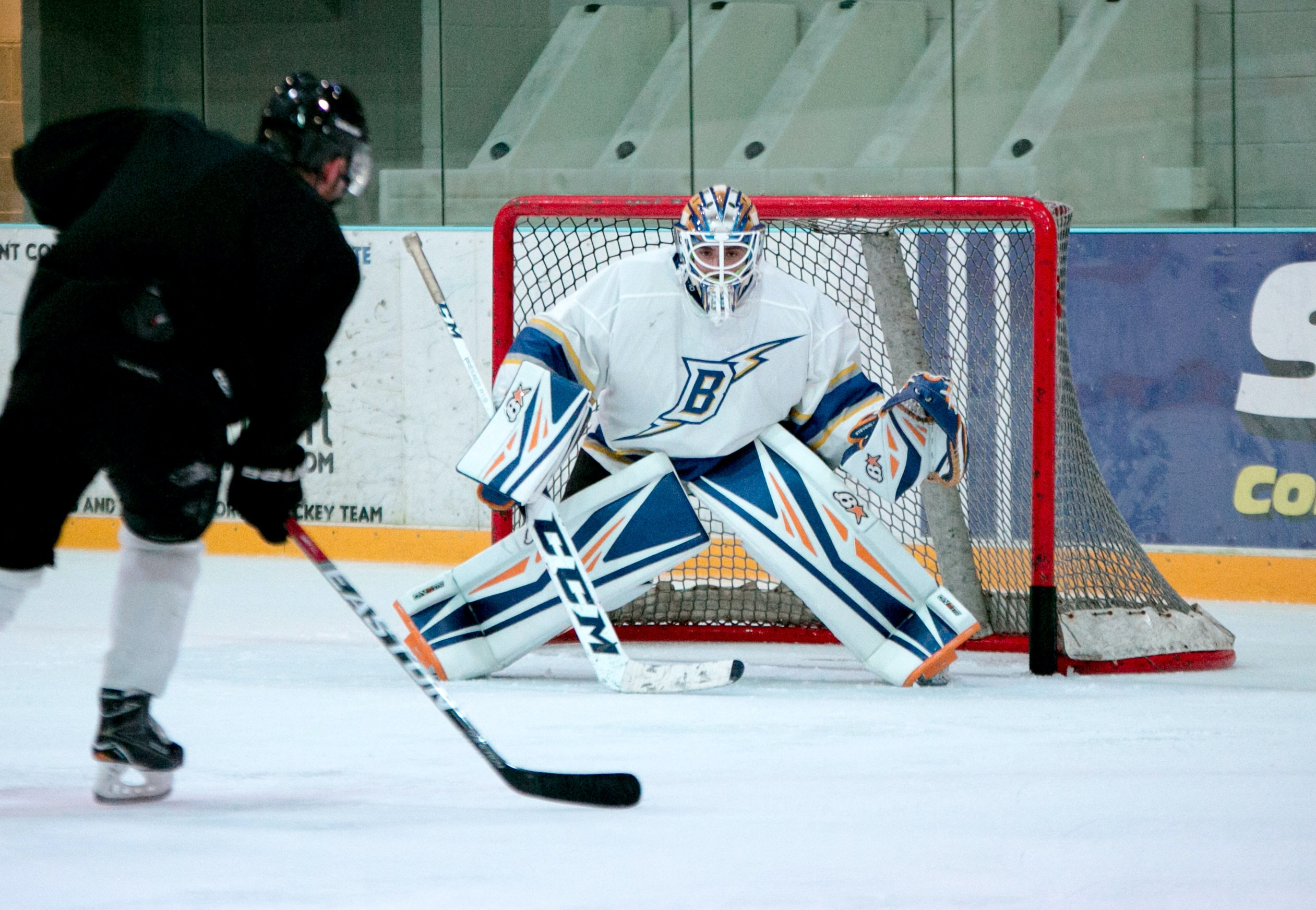 man taking aim for goal on hockey goalie
