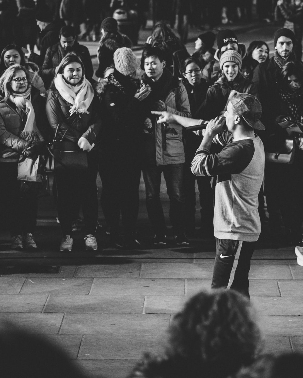 gray scale photo of man performing in front of people on street