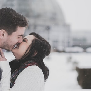 man and woman kissing in snow weather