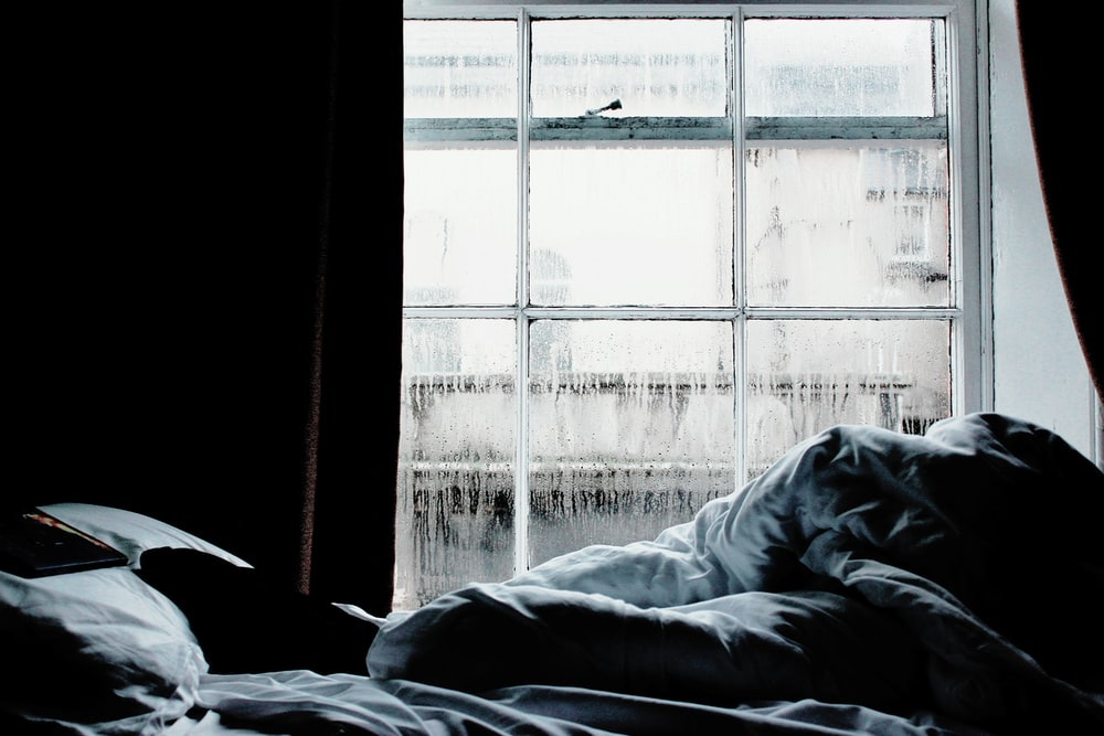 black and gray bed comforter near clear glass window