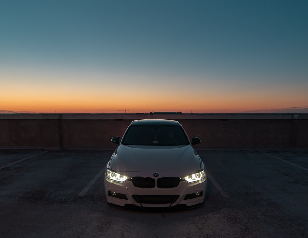 white BMW car near the wall parked
