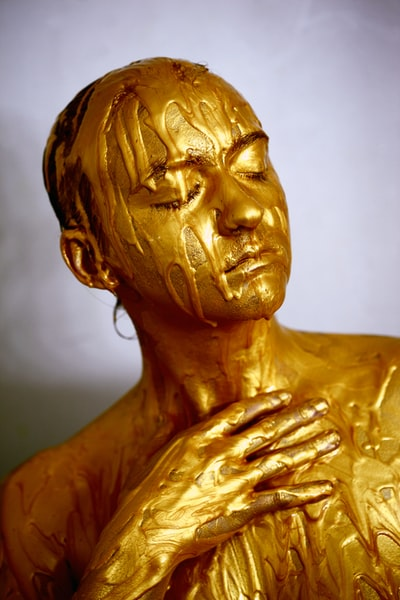 person coated with gold colored liquid posing