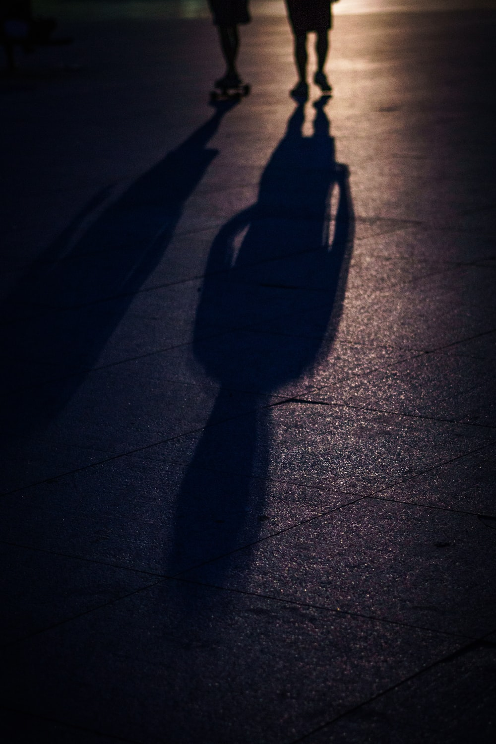 two people walking with shadows on road