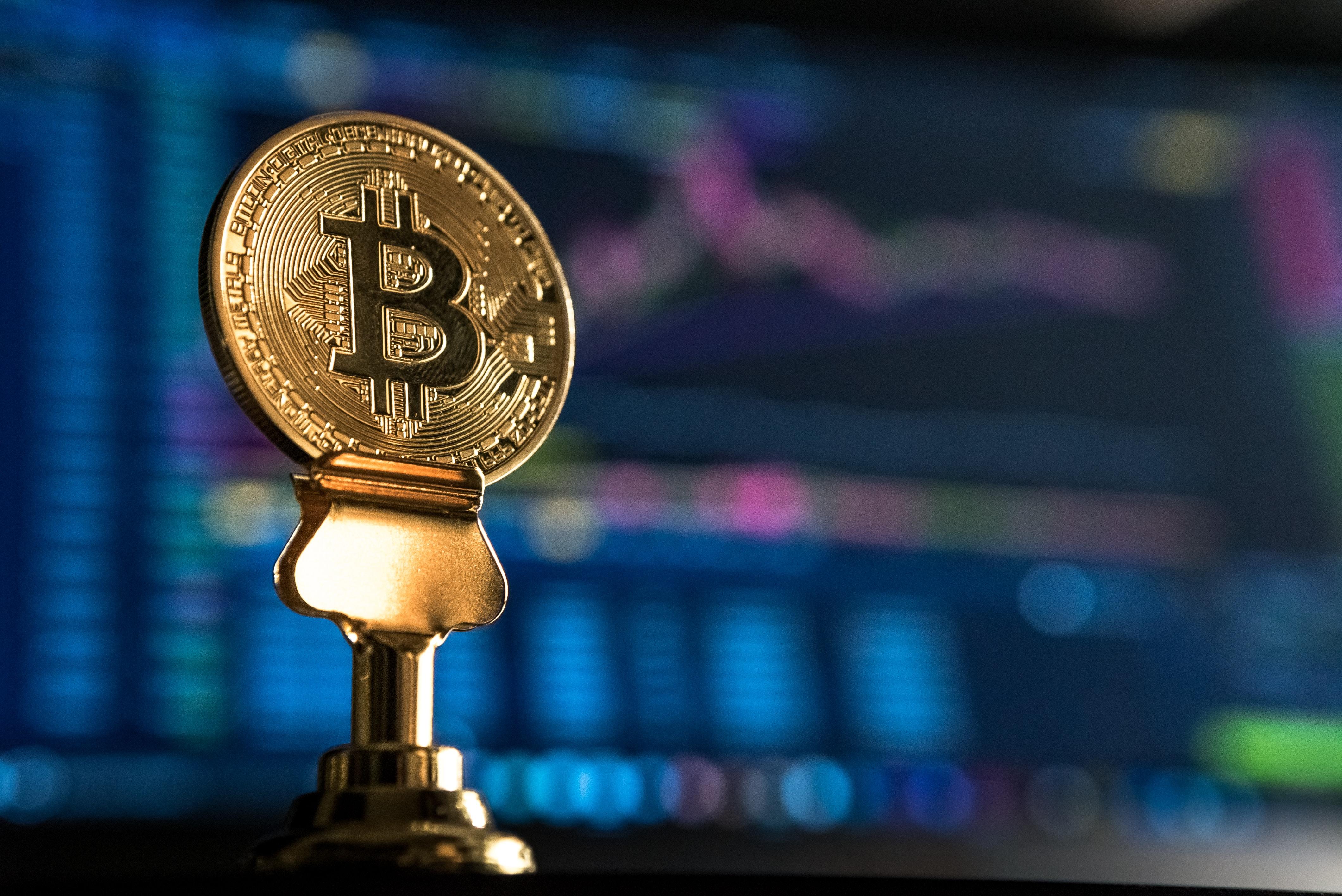 selective focus photo of Bitcoin near monitor
