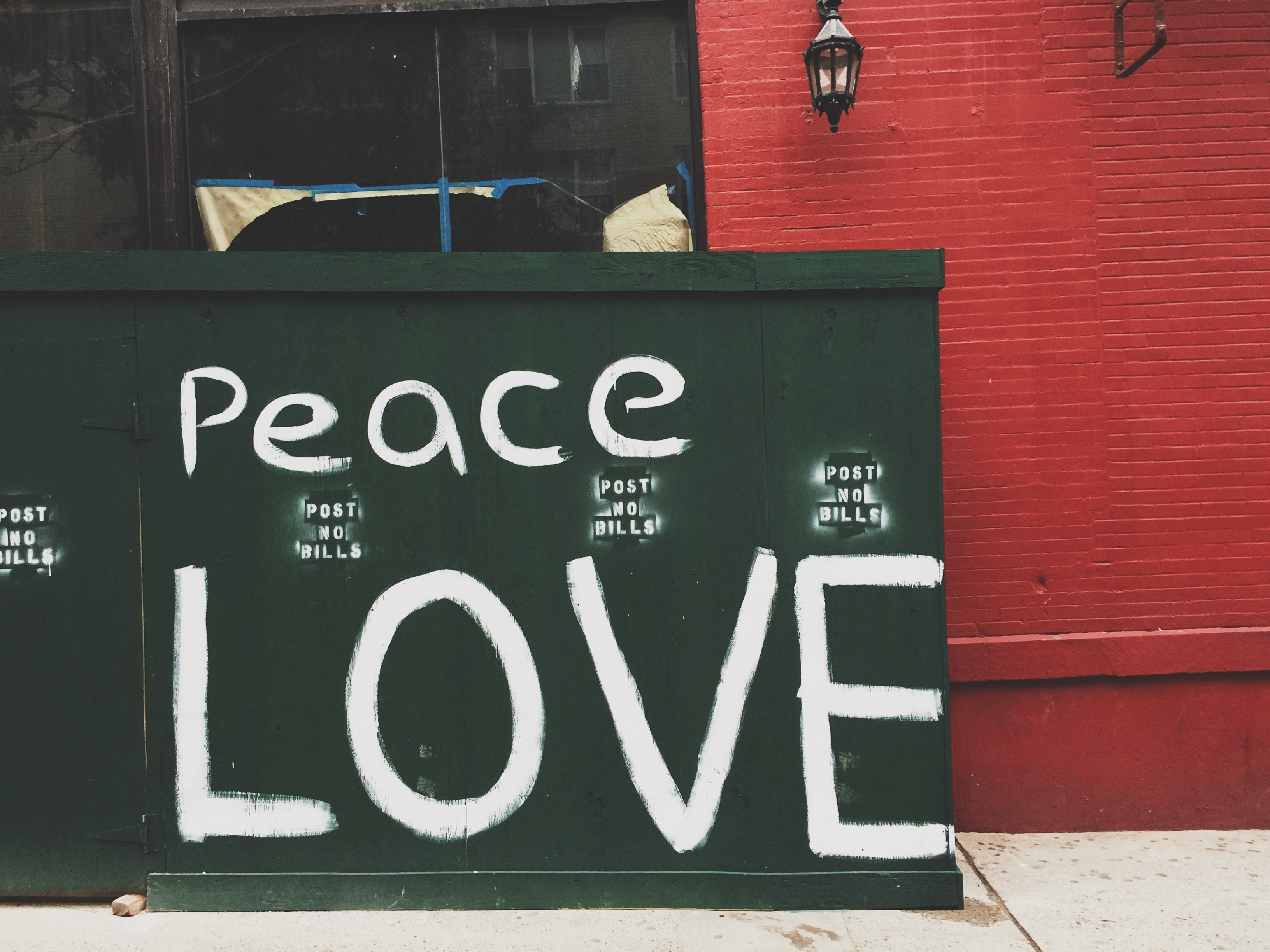 Peace Love painted on green wall