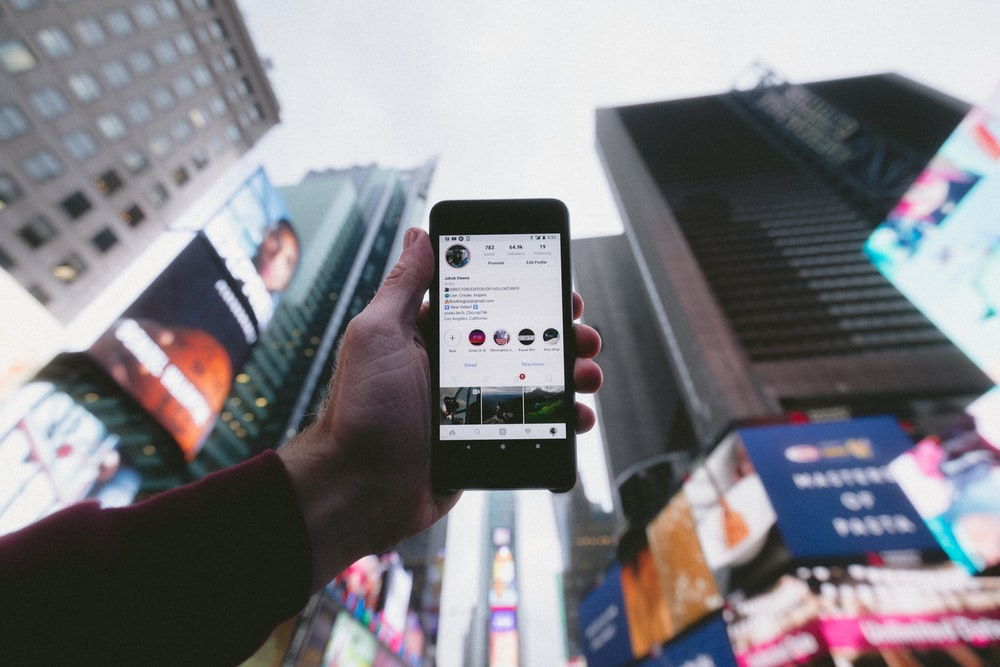 high angle photo of person holding turned on smartphone with tall buildings background