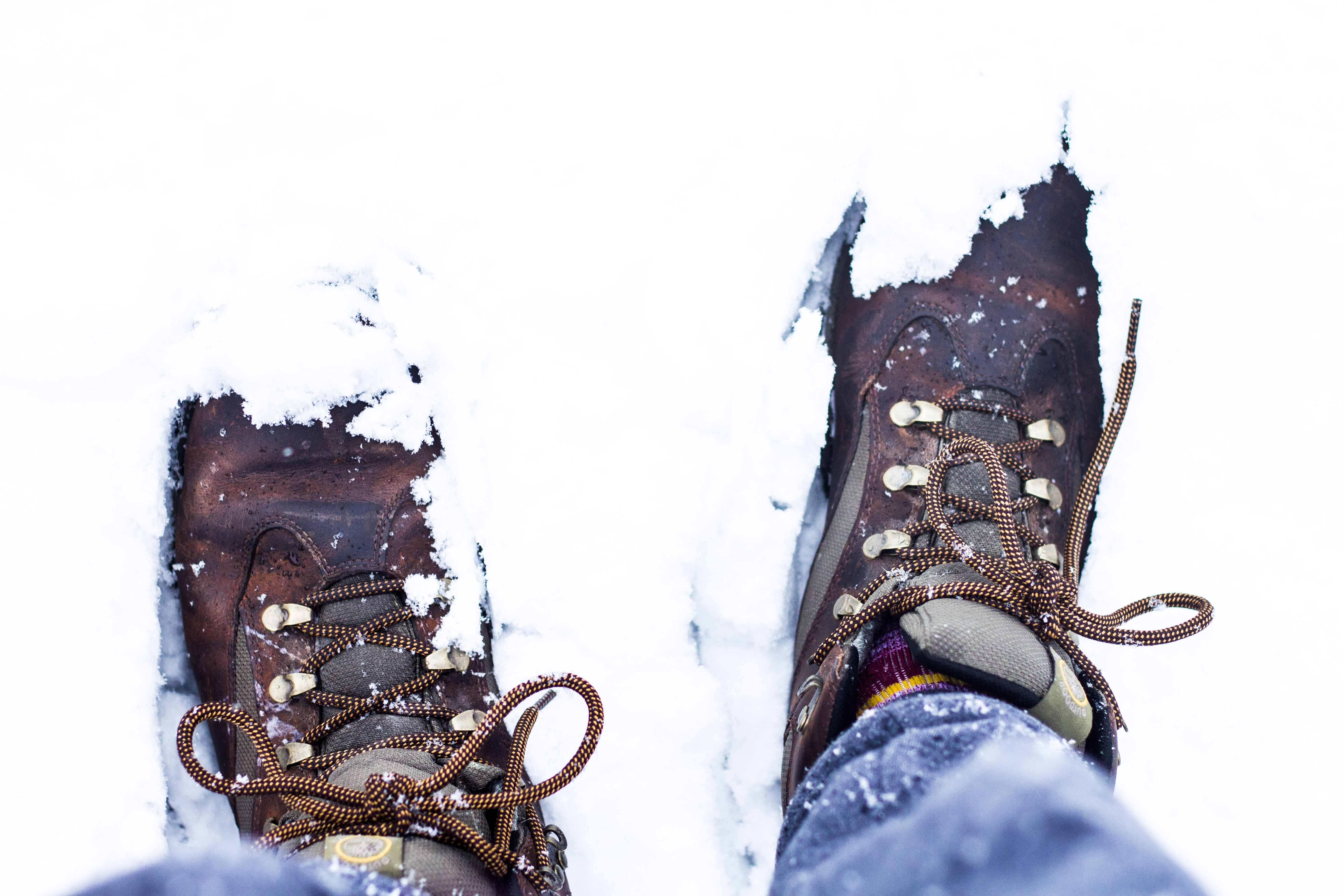 person wearing pair of brown shoes on snow