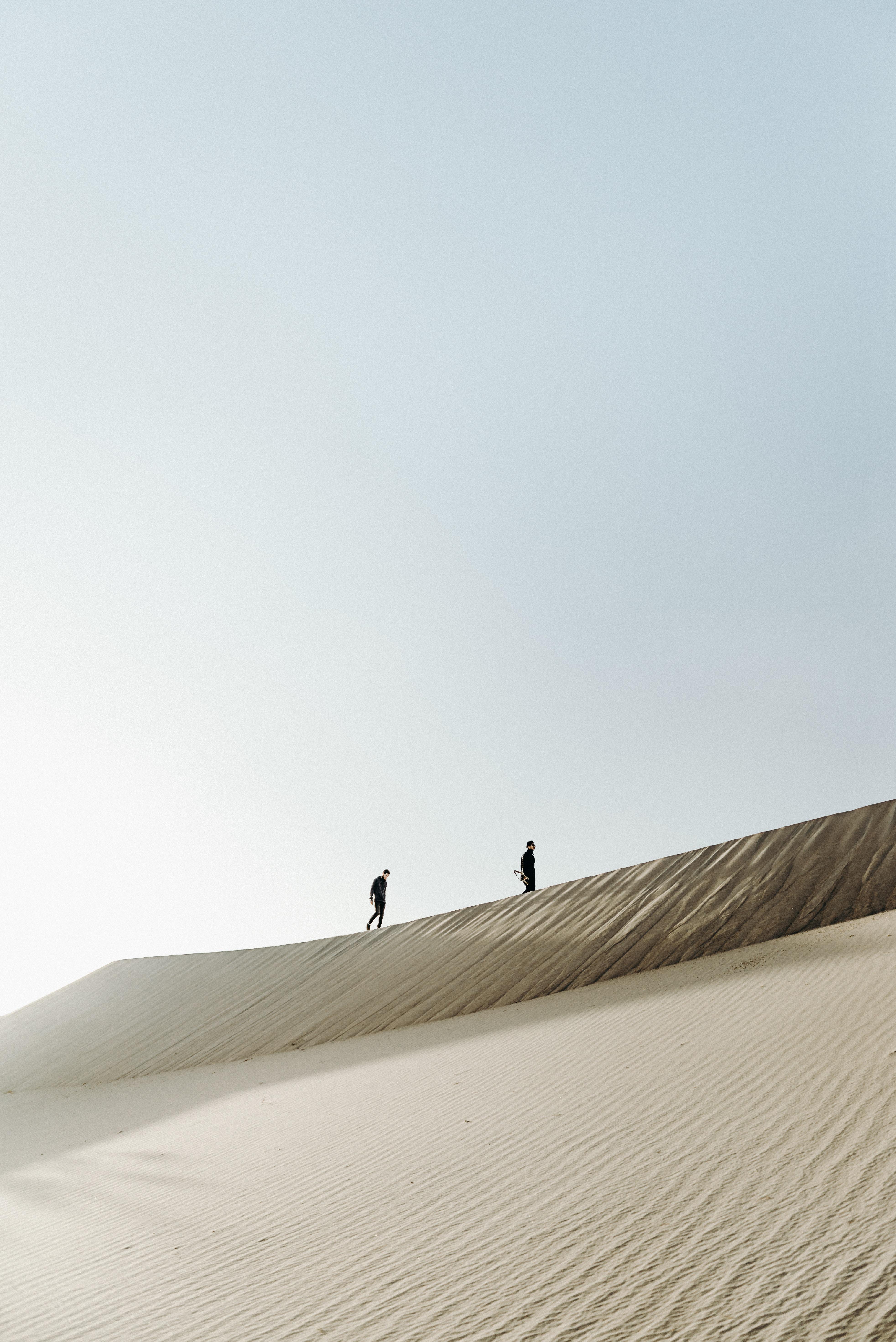 two men on the desert at daytime