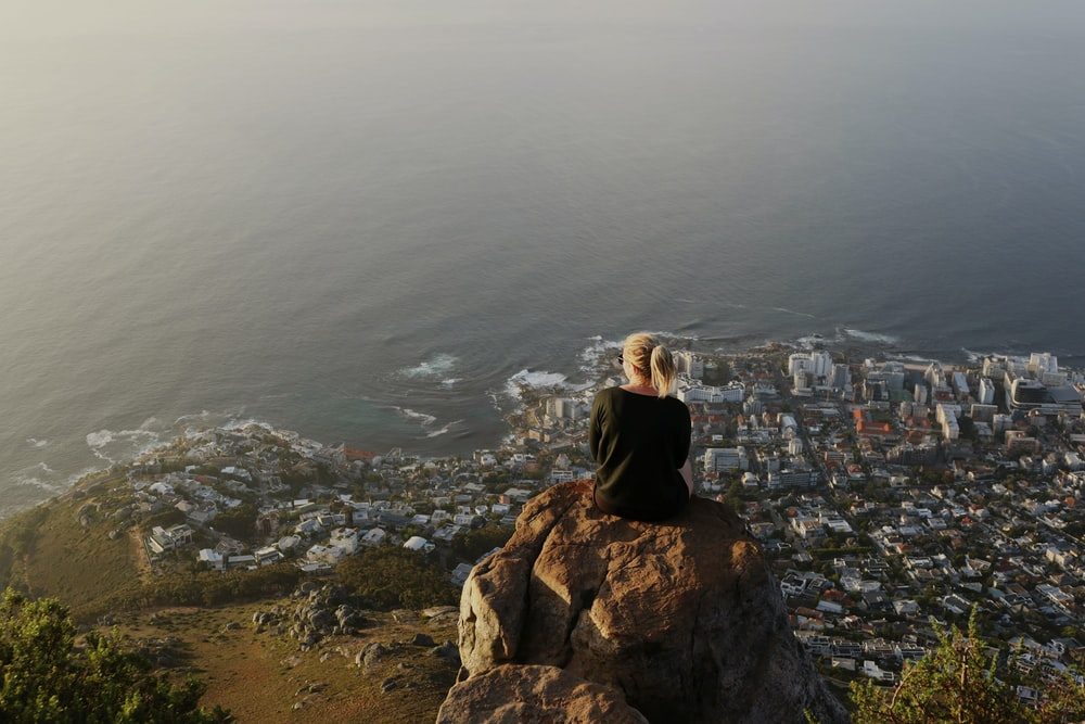 woman sitting on top of rocky mountain watching view of city